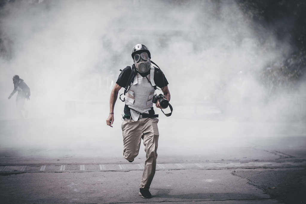A protester runs from tear gas fired by the Venezuelan national guard during an anti-government demonstration in 2017 in Caracas, Venezuela. © Enphoque