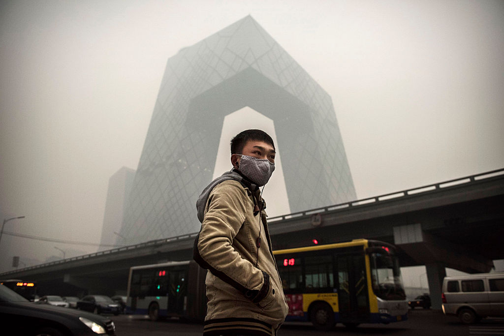 A Chinese man wears a mask as he waits to cross the road near the CCTV building during heavy smog  in Beijing, China. In 2014, United States President Barack Obama and China's president Xi Jinping agreed on a plan to limit carbon emissions by their countries, which are the world's two biggest polluters, at a summit in Beijing. © Kevin Frayer/Getty Images)