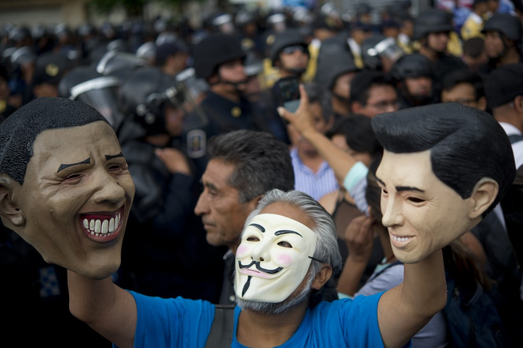 A masked teacher on strike raises masks of US President Barrack Obama (L) and Mexico's President Enrique Pena Nieto (R) in front of riot policemen during a demonstration in Mexico City on July 5, 2016. /AFP /YURI CORTEZ/Getty Images