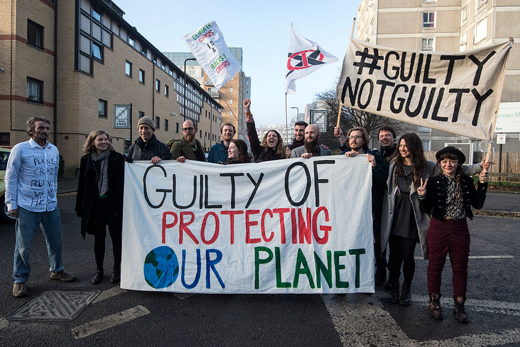 Defendants pose behind a banner outside Court before appearing on a charge of wilful obstruction after blocking a road near Heathrow Airport in protest at climate change on December 2016 in London, England. © Carl Court/Getty Images