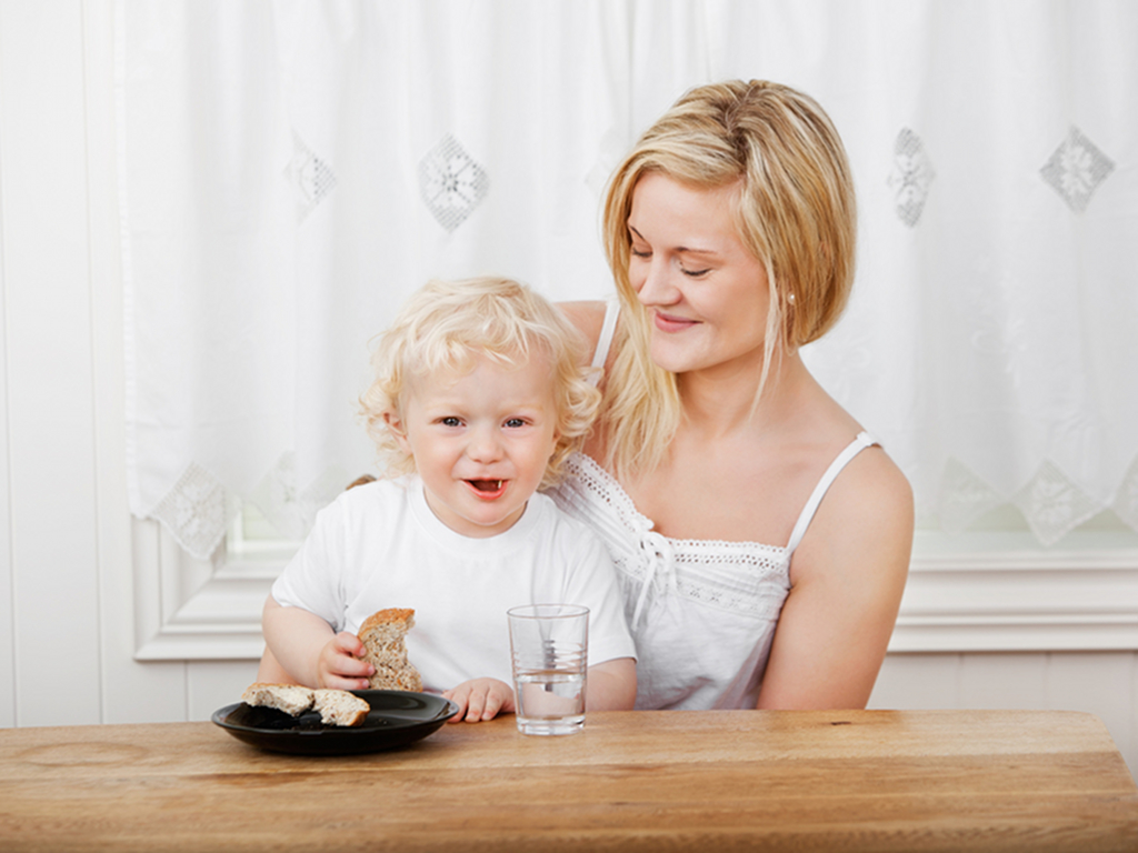 Happy beautiful mother with blond little boy eating bread